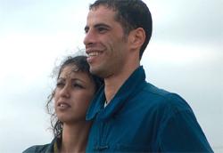 """Rachid Amrani in <i>Rome Plutot Que Vous</i>"""" />Ore 18.30 passaggio Gnomo. Aria gelida. Entro di corsa nel bar del cinema, mentre la serranda scende dolcemente. 5 euro di biglietto. M'immergo con la mia compagna d'avventure nella sala vuota e fredda. Hanno cambiato il film in programmazione. Volevamo vedere <em>Red Mistake</em> di Teshome Kebede Theodros (Etiopia, 2006) e, invece, viene proiettato <em>Rome Plutot Que Vous</em>, di Tariq Teguia (Algeria, 2006).<br /> <strong>Inizia il film. Non so bene cosa aspettarmi. Non ho mai visto un film algerino. </strong>Le scene sono lunghe e povere. Scarne di parole e di movimento. Si dipinge una realtà rumorosa e disperata. Case sfatte e stanche si stagliano sullo sfondo; il Sole caldo ed accecante della città africana frusta gli uomini che vi camminano sopra.<br /> Lunghe inquadrature indugiano su semplici gesti quotidiani: la preparazione del caffè, la pulizia di un corridoio, un viaggio in macchina. Il tutto dilatato ed esasperato nella sua banalità, nel suo scorrere inesorabile e semplice. </p> <p>Non manca qualche spunto originale. La ricerca della libertà e di un mondo sognato: l'Europa. Milioni di parabole televisive sono rivolte verso la terra promessa dove anche Kamel vuole tornare. E risulta tragicamente vera l'evidenza alla quale lo pone la sua ragazza Zina: lui vuole partire comunque, pagherà, anche se non è sicuro di arrivare. La speranza vale di più della realizzazione del sogno. <strong>Perché il cuore di un uomo ha il bisogno di sperare, di affrancarsi da una condizione di subalternità, per ritrovare la libertà perduta. </strong><br /> Ma quel mondo non è reale, è solo sognato. È un mondo fatto di Veline e di lussi impropri, che riluccicano bene sullo schermo del televisore, ma che rendono sempre più schiavi di sogni le persone che vi credono. </p> <p>Sebbene l'opportunità di riflettere sia preziosa, la realizzazione del film lascia alquanto a desiderare. Forse siamo noi che non siamo capaci di capirne il l"""