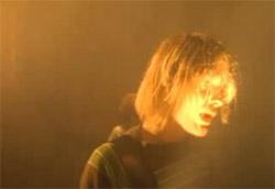 """<i>Nirvana – Smell like teen spirit</i>"""" />Nel 1991 i Nirvana esplosero con <em>Nevermind</em> e Samuel  Bayer imprigionò l'icona di Kurt Cobain in una nuvola di polvere rossa, in un circo stanco e vecchio, già a pezzi nella serata di maggior successo. <em>Smells like teen spirit.</em><br /> Bayer è riuscito a raccontare una canzone, un gruppo, ciò che stava diventando simbolo del musicista geniale e disperato con <strong>intensa corporeità, con nuda intimità, faccia a faccia con il performer, con la sua essenza.</strong> Una tinta che Bayer ha perfezionato e raffinato, creando alcuni dei più importanti videoclip musicali degli anni '90. Per poi sfociare nel capolavoro insieme ai Green Day con tutto <em><A href="""