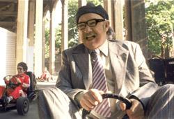 """Max Fisher, <i>Rushmore</i>"""" />più piani le storie si dipanano e si intrecciano. Gli attori, gli amici, i fratelli, la famiglia: i mondi di Wes Anderson diventano le storie di Owen Wilson, di Max Fisher, di Bill Murray, di Antony e Dignan, di Jason Schwartzman, dei Tenenbaum, di Anjelica Huston, dei Zissou, di Luke Wilson, dei fratelli Whitman. I legami si allungano attraverso tutti i film creando una firma autoriale e la storia filmica inizia a esistere oltre gli attori e i suoi creatori. O forse, proprio grazie alla loro pelle.</p> <p><strong>L'orizzonte e il tempo</strong><br /> Due segni andersoniani, due modi di vedere che si installano già dalle prime visioni. La """"banda"""" che spara con le pistole, che disegnano una traiettoria orizzontale nell'inquadratura; la scena del pestaggio di Dignan oltre il vetro rettangolare del pub spagnolo; il carrello dell'inserviente spagnola che prende tutta l'inquadratura uscendo nel fuoricampo; la professoressa Cross oltre il vetro della sua aula; il tuffo in piscina di Blume; lo spazio cementato dove atterra l'areoplanino di Max.<br /> <strong>I racconti di Anderson si sviluppano in orizzontale</strong>, anche quando sono su più piani, anche quando la profondità acquista il potere di narrare contemporaneamente più personaggi e più scene. La tensione di Anderson è quella di condurre i personaggi da un punto all'altro della loro vita, lungo una linea diritta, curiosa ma diritta.<br /> L'evoluzione rassicurante dei suoi personaggi, che finiscono, inevitabilmente """"da qualche parte"""" viene sottolineata e resa eterna dai suoi <strong>ralenti espressivi, che dilatano il momento senza che ne si perda la purezza</strong>.<br /> <img class="""
